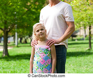 Cute little girl with her father in a park