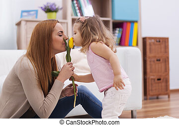 Cute little girl with her mother smelling fresh tulip