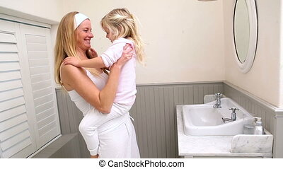 Cute little girl with her mother at home in bathroom
