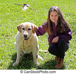 cute little girl with labrador dog on the grass