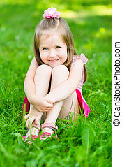 Cute little girl with long blond hair, sitting on grass