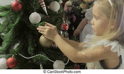 Cute little girl with long hair and beautiful headband  decorates a Christmas tree with baubles