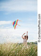 Cute little girl with long hair holding kite in the field on summer sunny day