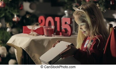 Cute little girl with long hair wearing in sweater with snowmen opens a box with magic in the dark on the new year