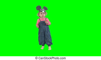 Cute little girl with mouse hat eating sweet ring shaped roll isolated on green