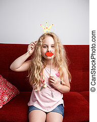 Cute little girl with paper crown and red lips is sitting on red chair at home.