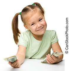 Cute little girl with paper money - dollars - Cute cheerful...