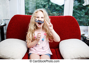 Cute little girl with paper mustaches while sitting on red chair at home.