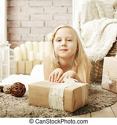 Cute little girl with present at home