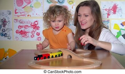 Cute little girl with pretty mother pushing toy train...