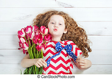 Cute little girl with red tulips and giving air kiss.