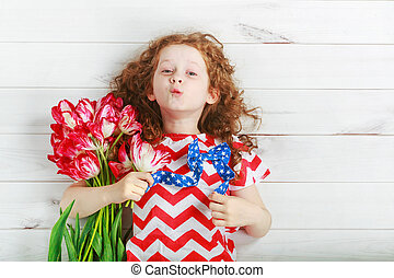 Cute little girl with red tulips on celebrating 4th july. Independence Day concept.