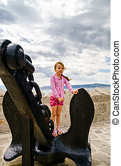 Cute little girl with ship anchor on the seaside