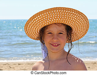 little girl with straw hat by the sea in summer