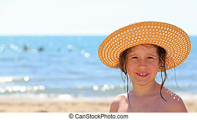 cute little girl with straw hat by the sea