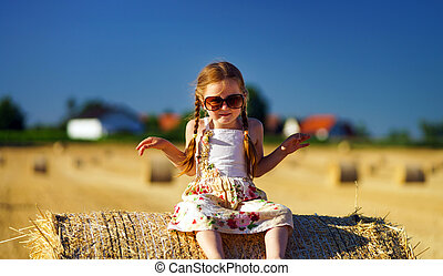Cute little girl with sunglasses posing on the haystack