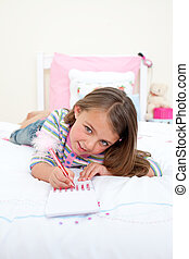 Cute Little girl writing on a notebook lying on her bed