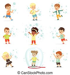 Cute little girls and boys blowing and playing soap bubbles....