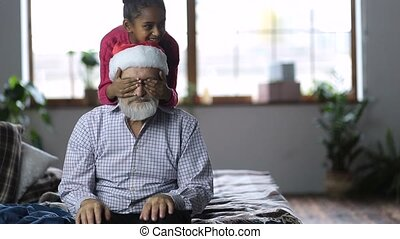 Cute little girls giving christmas gift to grandpa
