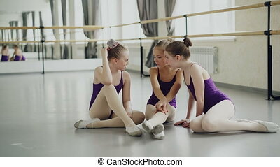 Cute little girls in leotards and pointe shoes are talking sitting on floor during break between ballet lessons in art school. Children are emotional smiling and chatting.