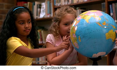 Cute little girls looking at globe