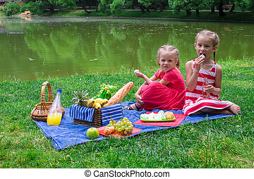 Cute little girls picnicing in the park at sunny day