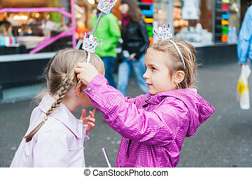Cute little girls playing princesses in a city