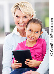 granddaughter and grandmother with tablet pc