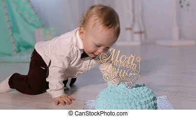 Cute little handsome boy is playing with the first cake sitting on the floor.