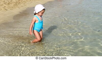 Cute little happy child playing in sea waves