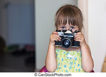 Cute little happy girl with vintage photo camera