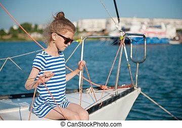 cute little healthy child in sunglasses sitting aboard luxury recreational boat