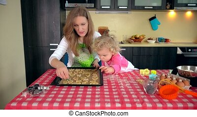 cute little helper girl with beautiful mother place cookies into oven tin