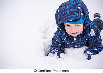 Cute little kid boy in colorful winter clothes making snow angel, laying down on . Active outdoors leisure with children in . Happy child.