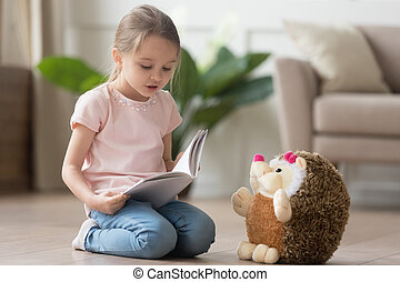 Cute little kid girl playing alone reading book to toy