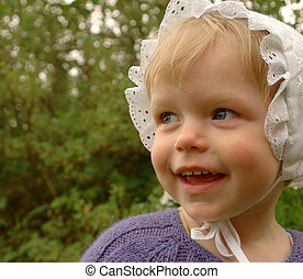 Cute little kid in a bonnet on green background