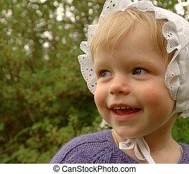 Cute little kid in a bonnet on green background