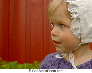 Cute little kid in a bonnet on red background