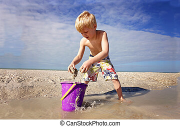 Cute Little Kid Playing with Sand in a Bucket at the Beach by the Ocean