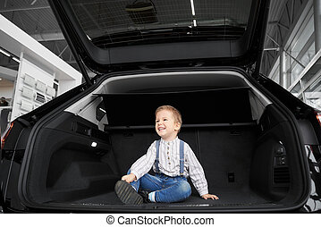 Cute little kid sitting in luggage space of car in showroom.