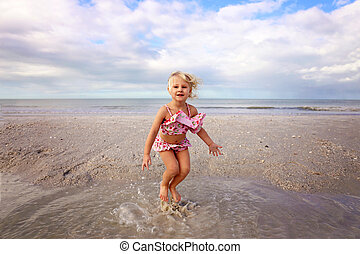 Cute Little Kid Splashing and Playing in the Water on the Beach by the Ocean