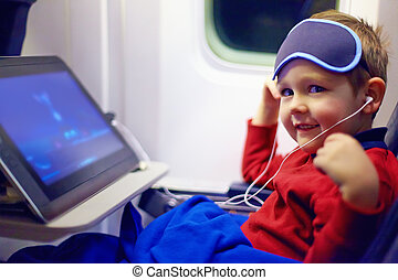 cute little kid watching cartoons during the long flight in airplane