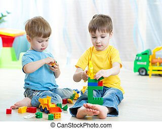 Cute little kids play with building bricks in preschool