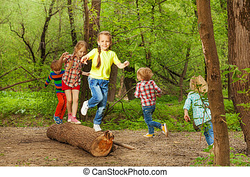 Cute little kids playing on a log in the forest