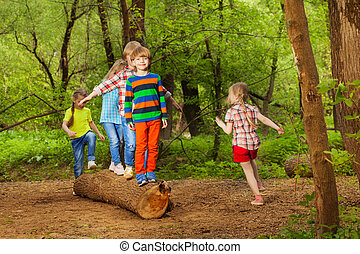 Cute little kids walking on log of tree in park