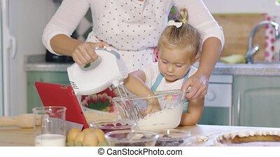 Cute little kitchen helper helping her Mum with the baking...