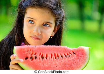 Cute little latin girl eating watermelon