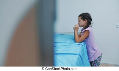 Cute little lifestyle girl praying at home. little girl prays in the evening before bedtime bed. little girl and religion concept Faith in God