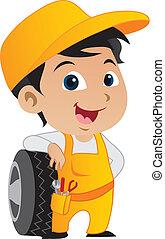 Cute little mechanic boy leaning against a car's tire