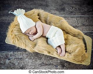 Cute little, newborn child sleeping on the soft blanket